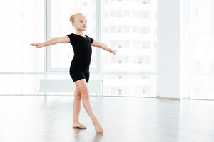 Little cute girl is busy performing exercises in the studio