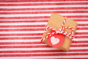 Little gift box with heart shaped tag on red and white striped background