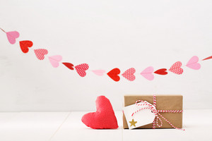 Little gift box with hearts hanging above for valentine gift theme
