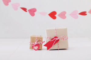 Little gift boxes with hearts hanging above for valentine gift theme