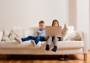 Little girl and boy sitting on sofa with a laptop computer at home. Happy children playing indoors using PC.