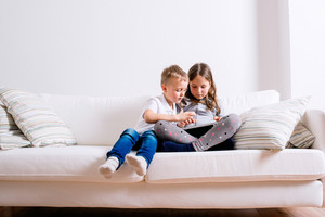 Little girl and boy sitting on sofa with a tablet. Happy children playing indoors.