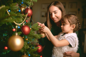 Little girl and her mother decorating Christmas tree