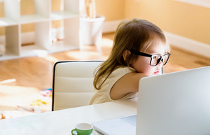 Little girl at her desk and computer at home