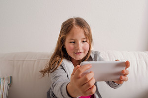 Little girl at home sitting on sofa with a smart phone, taking selfie. Happy child playing indoors.