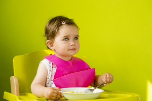 Little girl in highchair is eating snack in the kitchen