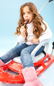 Little girl in winter clothes eating ice-cream while sitting on sledge