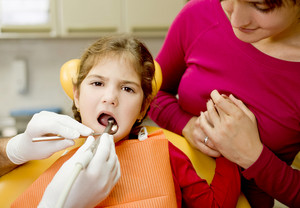Little girl is having her teeth checked by dentist