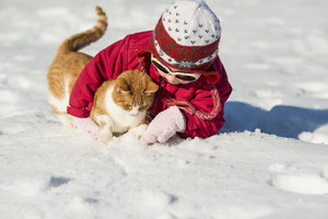 Little girl is playing outside in cold winter.