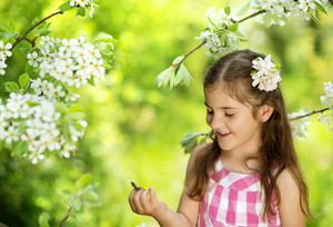 Little girl is playing with butterfly in nature