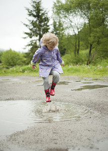 Little girl jumping in a water puddle in green park
