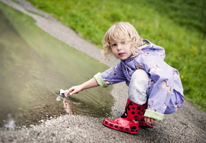 Little girl playing in a water puddle with a paper boat