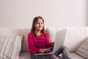 Little girl sitting on sofa with a laptop computer at home. Happy child playing indoors using PC.
