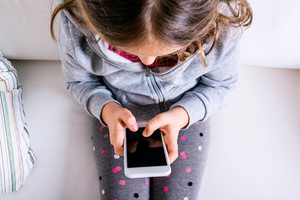 Little girl sitting on sofa with a smart phone. Happy child playing indoors.
