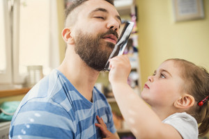 Little girl styling beard of her father