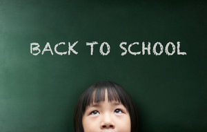 Little girl with Back to school concept on the blackboard background.