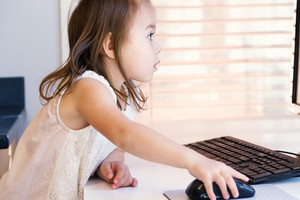 Little girl with her desktop computer at home