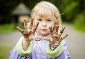Little girl with her muddy hands in green park