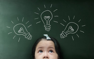 Little girl with light bulb on the blackboard background.