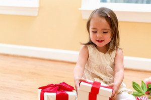 Little girl with present boxes at home
