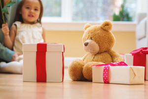 Little girl with teddy bear and present boxes at home