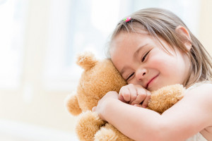 Little girl with teddy bear at home