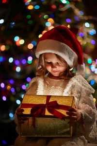 Little Santa with giftbox on sparkling background