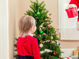 Little toddler girl getting a gift from Santa Claus by the Christmas tree