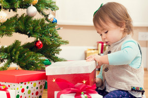 Little toddler girl gifts presents under her Christmas tree