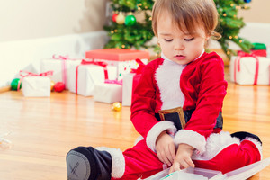 Little toddler girl in a santa costume playing under the Christmas tree