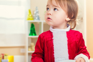 Little toddler girl in a Santa costume ready for Christmas