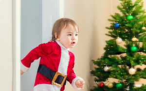 Little toddler girl in a santa suit dashing to open her Christmas presents