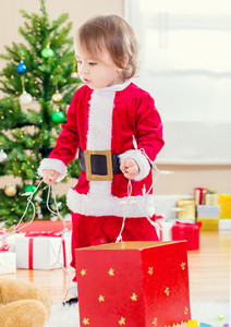 Little toddler girl in a santa suit playing by the Christmas tree
