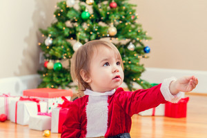 Little toddler girl in a santa suit playing under the Christmas tree