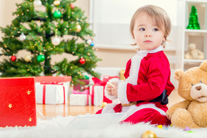 Little toddler girl in a santa suit playing with her Christmas toys