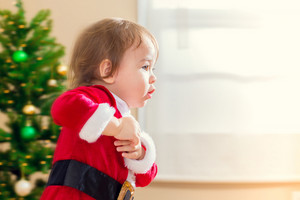 Little toddler girl in a santa suit running to open Christmas presents
