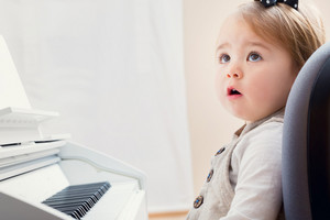 Little toddler girl in awe of the piano