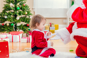 Little toddler girl interacting with Santa Claus by the Christmas tree