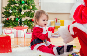 Little toddler girl meeting Santa Claus by the Christmas tree