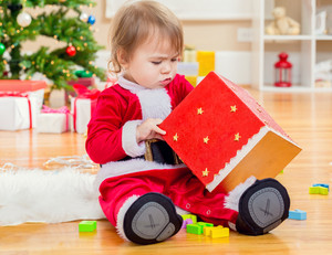 Little toddler girl opening a big present box under by her Christmas tree