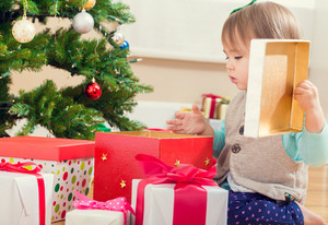 Little toddler girl opening a big present under her Christmas tree