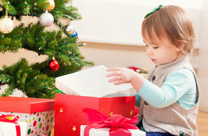 Little toddler girl opening a Christmas present