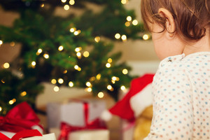 Little toddler girl opening gifts in front of the Christmas tree