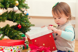 Little toddler girl opening presents under her Christmas tree