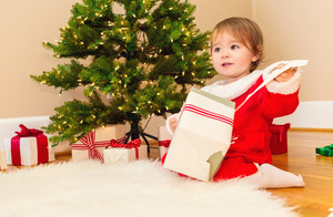 Little toddler girl opening presents under the Christmas tree