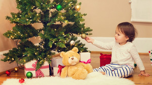 Little toddler girl playing by the Christmas tree
