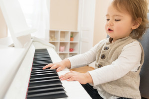 Little toddler girl playing piano in her house