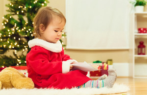 Little toddler girl playing with Christmas decorations in her home