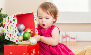 Little toddler girl playing with Christmas decorations