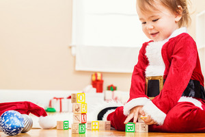 Little toddler girl playing with her Christmas toys with a santa costume